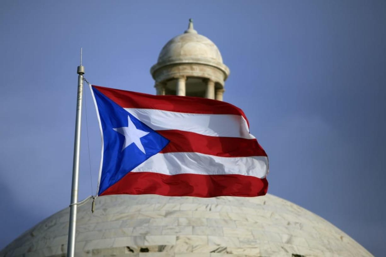 FILE - In this July 29, 2015 file photo, the Puerto Rican flag flies in front of Puerto Rico's Capitol as in San Juan, Puerto Rico. A senior Puerto Ricon official said Tuesday, Feb. 11, 2020, that the island's government has lost more than $2.6 million after falling for an email phishing scam.