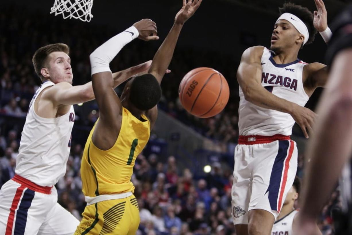 San Francisco guard Jamaree Bouyea, center, has his shot blocked by Gonzaga guard Admon Gilder, right, while also pressured by forward Filip Petrusev during the first half of an NCAA college basketball game in Spokane, Wash., Thursday, Feb. 20, 2020.