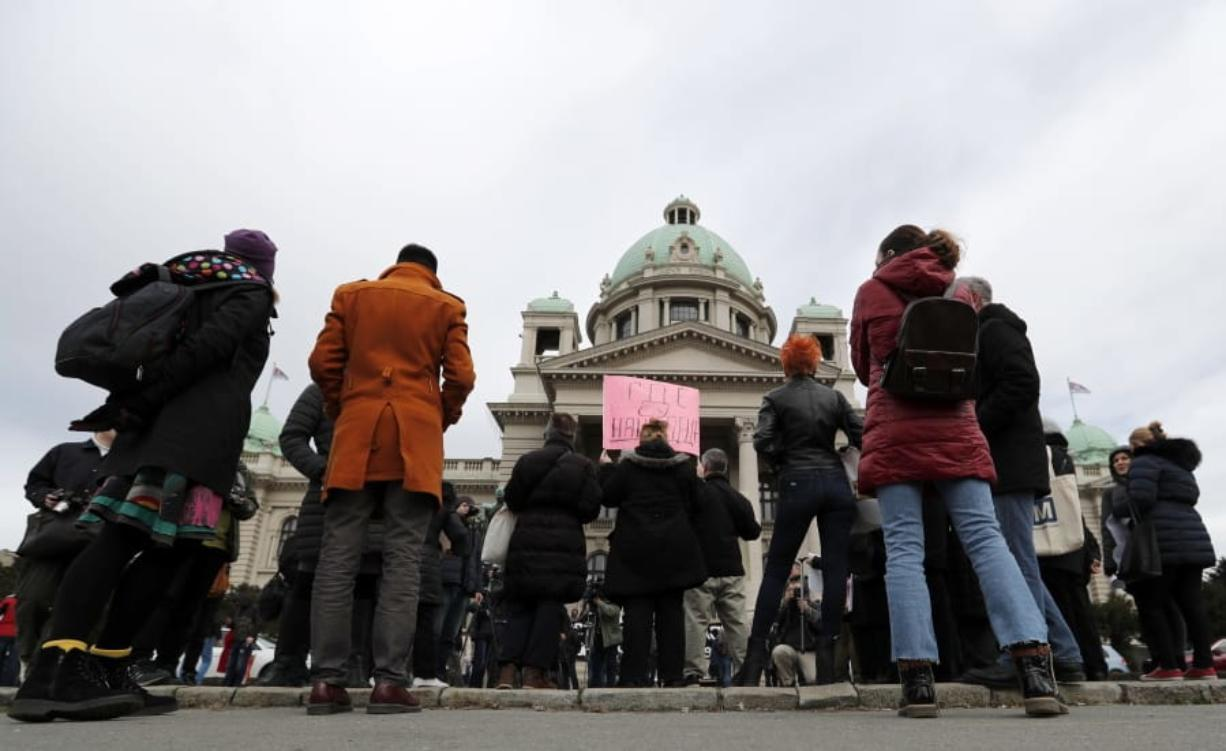 """In this photo taken Monday, Feb. 24, 2020, a participant holds a banner that reads: """"Where are our Children"""", during a protest in front of the parliament building in Belgrade, Serbia."""