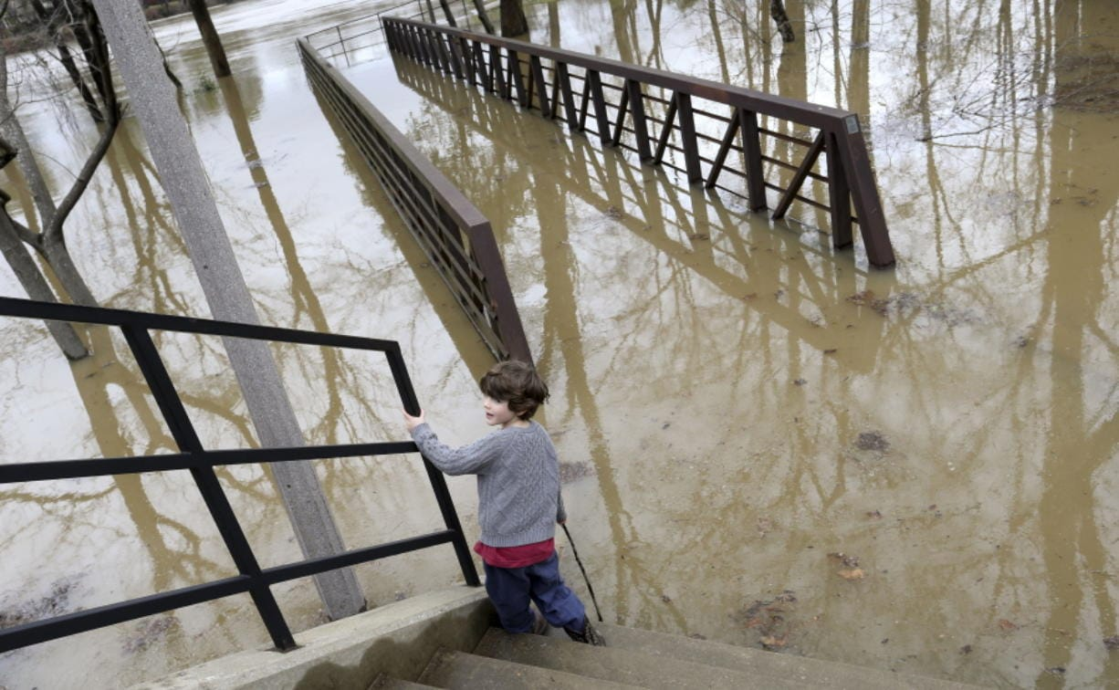 Heavy rains fell Monday leaving the Tuscaloosa, Ala., area with high water and washed out roads, Tuesday, Feb. 11, 2020. Gideon Altman plays near a flooded section of the Tuscaloosa Riverwalk under the supervision of his mother as waters from the Black Warrior River rise. Children in Tuscaloosa City and County schools got a day off due to the flooding. (Gary Cosby Jr./The Tuscaloosa News via AP)