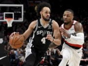 San Antonio Spurs guard Derrick White, left, drives to the basket against Portland Trail Blazers guard Damian Lillard, right, during the first half of an NBA basketball game in Portland, Ore., Thursday, Feb. 6, 2020.