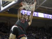 Stanford's Oscar da Silva hangs from the basket after dunking against Washington late in the second half of an NCAA college basketball game Thursday, Feb. 20, 2020, in Seattle. Stanford won 72-64.