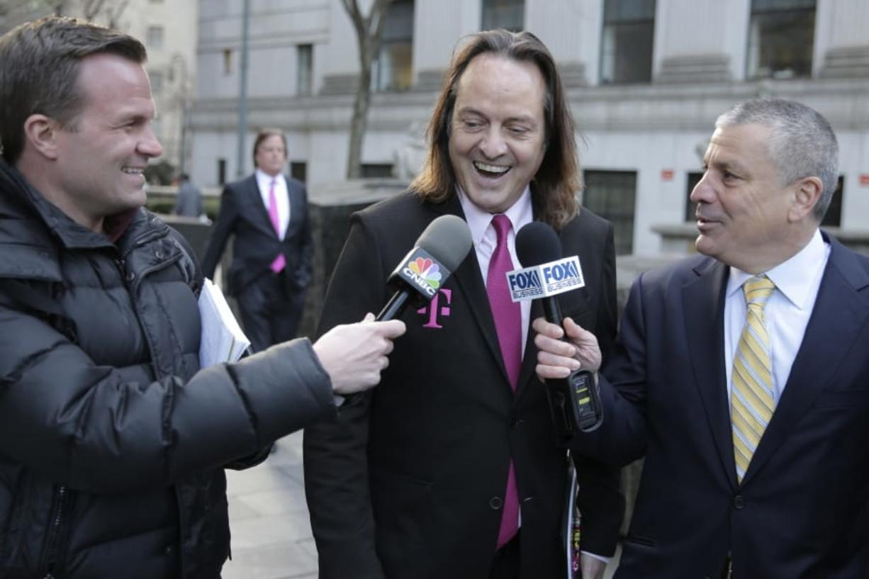 FILE - In this Jan. 15, 2020, file photo T-Mobile chief executive John Legere speaks to reporters as he leaves the courthouse in New York. A federal judge has removed a major obstacle to T-Mobile's $26.5 billion takeover of Sprint, as he rejected claims by a group of states that the deal would mean less competition and higher phone bills.