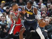 Denver Nuggets forward Jerami Grant, right, works the ball inside as Portland Trail Blazers guard Damian Lillard defends in the first half of an NBA basketball game Tuesday, Feb. 4, 2020, in Denver.