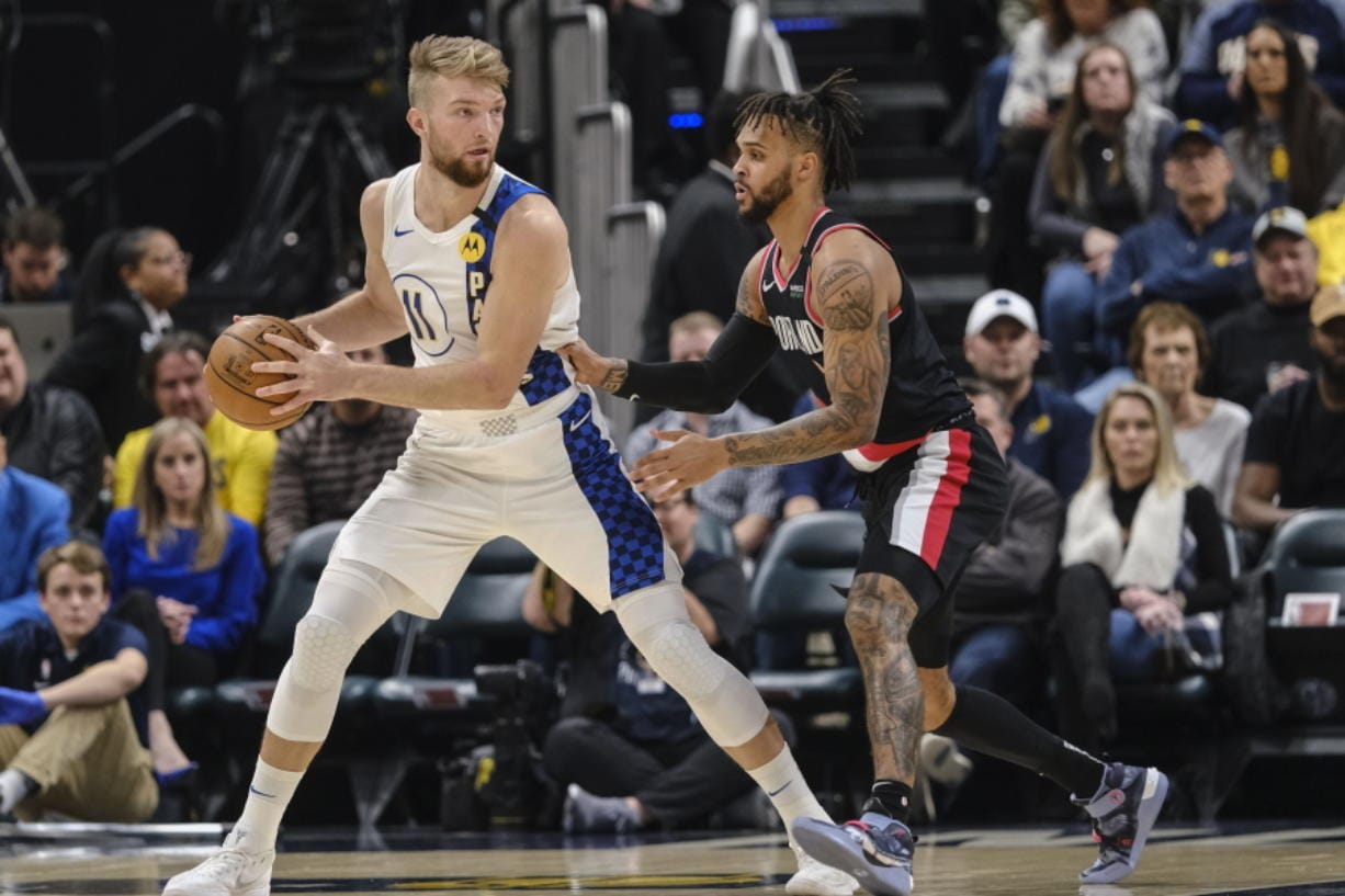 Indiana Pacers forward Domantas Sabonis, left, looks to pass around Portland Trail Blazers center Moses Brown during the first half of an NBA basketball game in Indianapolis, Thursday, Feb. 27, 2020.