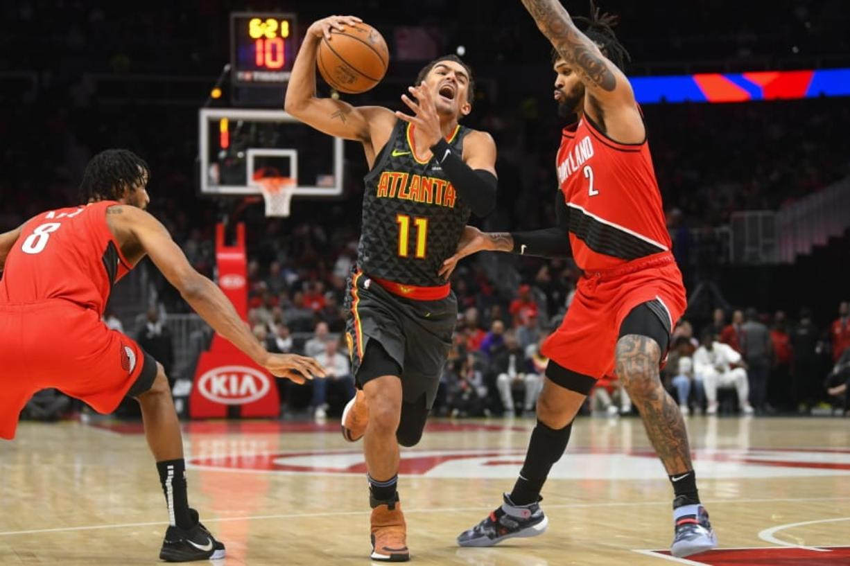 Atlanta Hawks guard Trae Young (11) tries to penetrate the defense of Portland Trail Blazers forward Trevor Ariza (8) and guard Gary Trent Jr. (2) during the first half of an NBA basketball game Saturday, Feb. 29, 2020, in Atlanta.