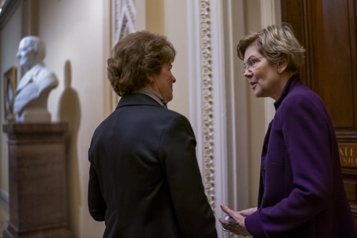Democratic presidential candidate Sen. Elizabeth Warren, D-Mass., right, confers with Sen. Jeanne Shaheen, D-N.H., during a series of votes on the war powers resolution which asserts that President Donald Trump must seek approval from Congress before engaging in further military action against Iran, on Capitol Hill in Washington, Thursday, Feb. 13, 2020. (AP Photo/J. Scott Applewhite)