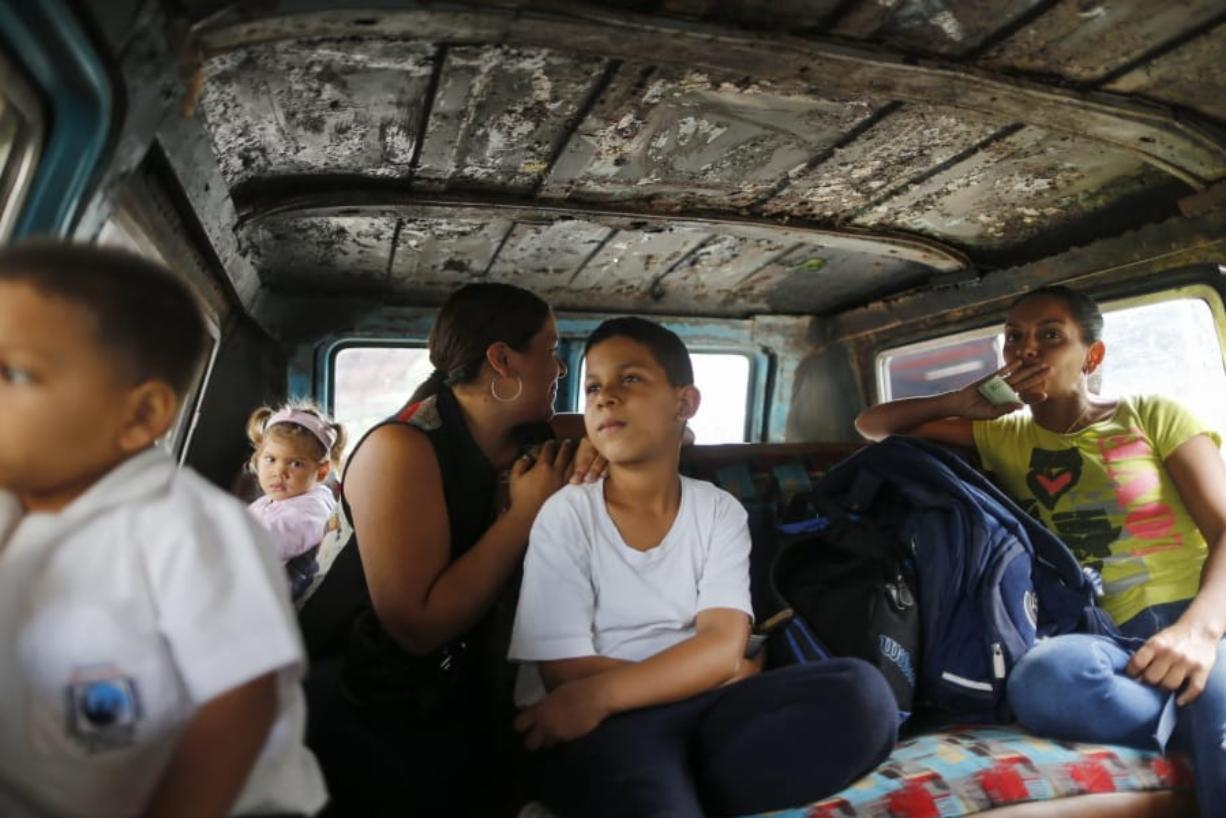 Passengers ride on public transport in Caracas, Venezuela, Wednesday, Feb. 19, 2020. The debate over fresh U.S. sanctions aimed at forcing out Venezuela's Nicolas Maduro played out Wednesday across the crisis-stricken South American nation. Families have been split up with at least 4.5 million Venezuelans fleeing crumbling public services. (AP Photo/Ariana Cubillos)