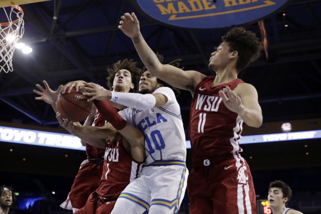UCLA guard Tyger Campbell (10) vies for a rebound against Washington State guard Jervae Robinson (1) and forward DJ Rodman (11) during the first half of an NCAA college basketball game Thursday, Feb. 13, 2020, in Los Angeles.