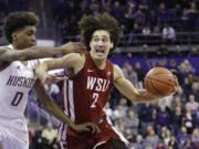 Washington State's CJ Elleby (2) drives against Washington's Jaden McDaniels (0) during the second half of an NCAA college basketball game Friday, Feb. 28, 2020, in Seattle. Washington State won 78-74.