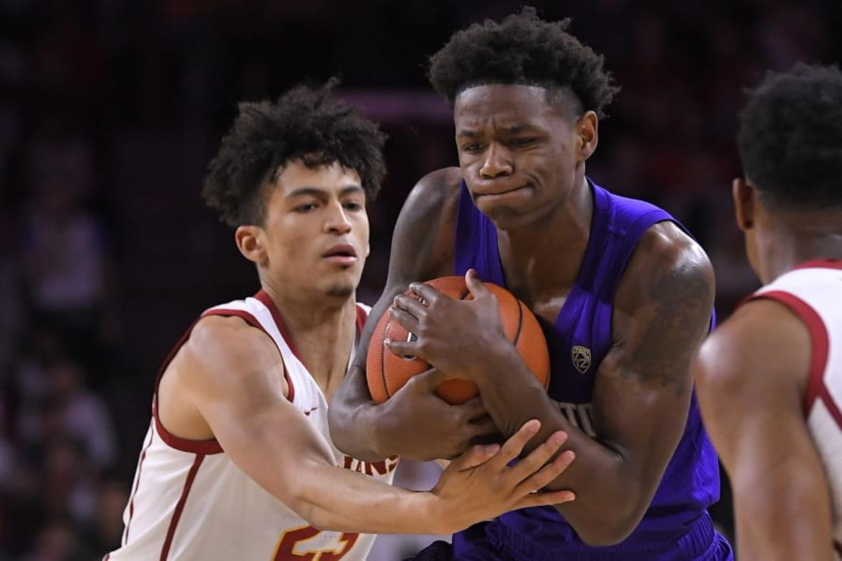 Southern California forward Max Agbonkpolo, left, ties up Washington guard Nahziah Carter during the first half of an NCAA college basketball game Thursday, Feb. 13, 2020, in Los Angeles. (AP Photo/Mark J.
