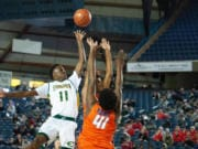 Evergreen's Mario Herring lifts a floater over a pair of Rainier Beach defenders in a 3A round of 12 game on Wednesday at the Tacoma Dome.