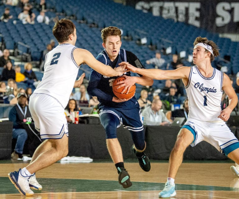 Skyview's Kyle Gruhler is fouled as he drives between Olympia's Zack Swanson, left, and Ethan Gahm. Gruhler finished with 23 points in the 4A State consolation round defeat. (Joshua Hart/The Columbian)