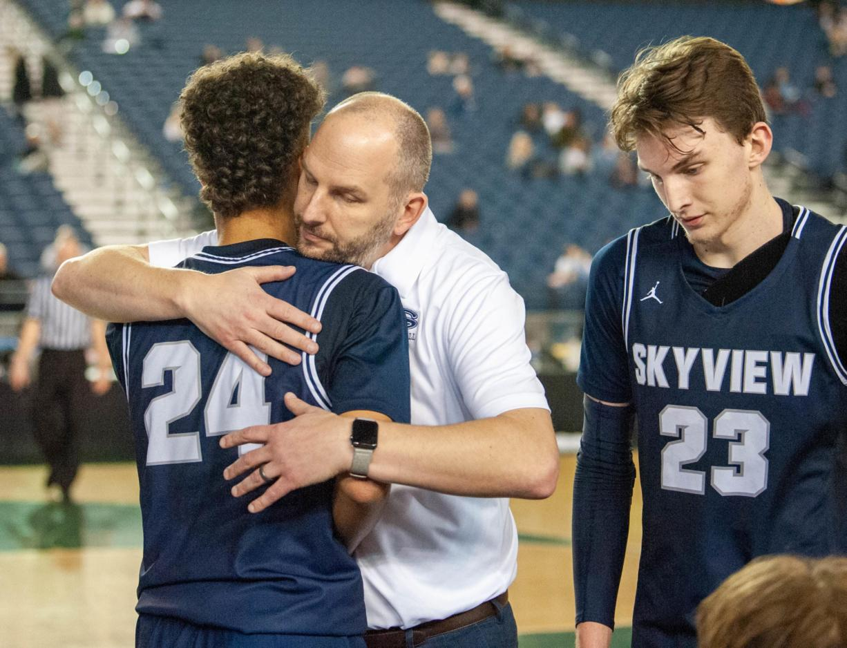 Skyview's Jace Chatman receives a hug from coach Matt Gruhler in a 4A State consolation game Friday at the Tacoma Dome. Skyview lost 75-55 to Olympia to end its season.