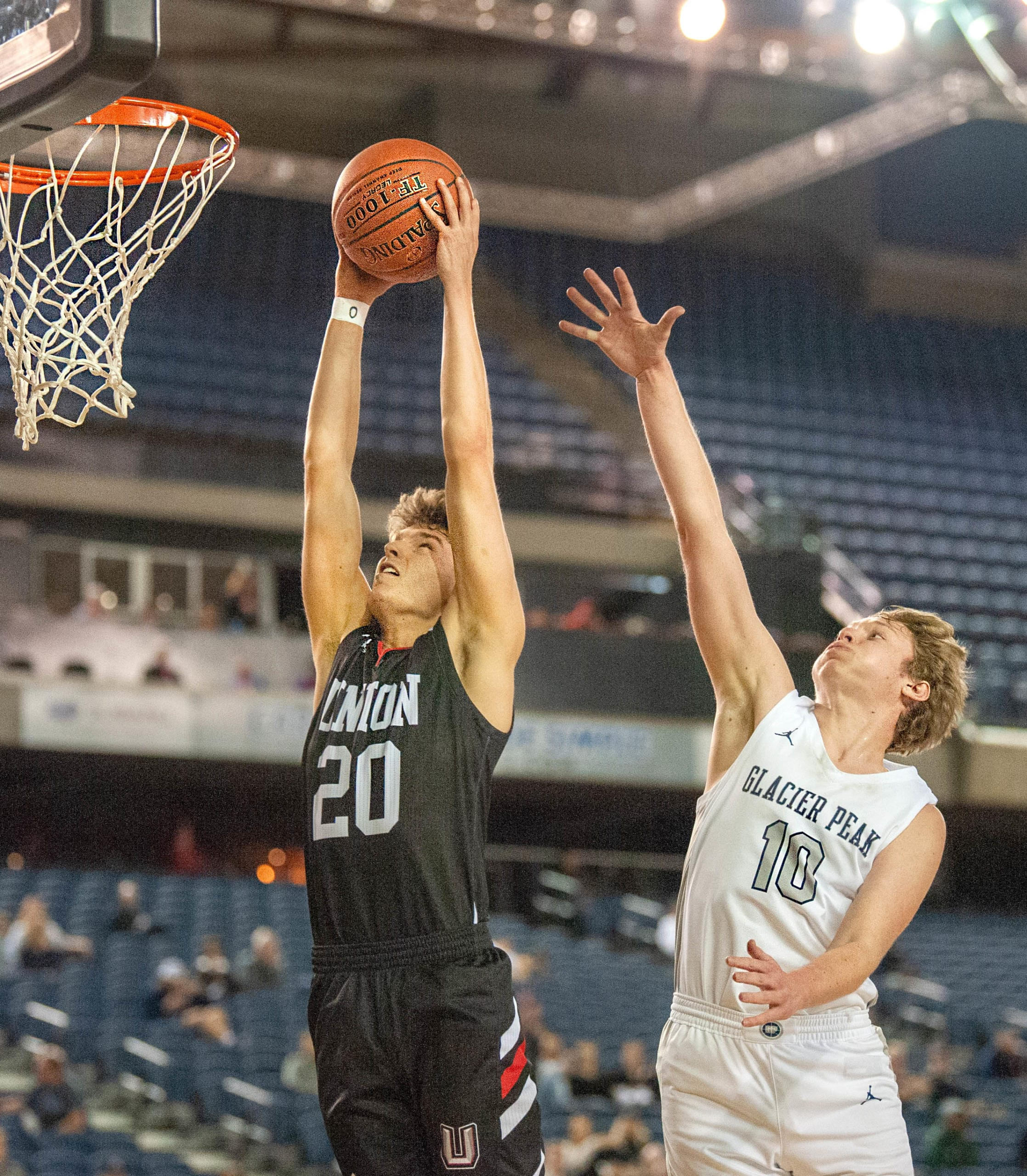 Union's Josh Reznick rises up for a dunk as Glacier Peak's Tristan Bates tries to defend in the TItans' 63-49 in the 4A State trophy game on Saturday at the Tacoma Dome. (Joshua Hart/The Columbian)