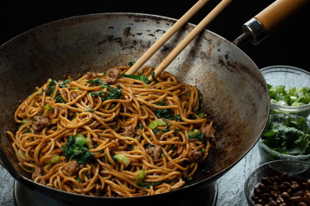 Noodles are tossed in an oil flavored with Sichuan peppercorns, then finished with peanuts, green onions, cilantro, garlic and more peppercorns but this time ground into a powder. (E.