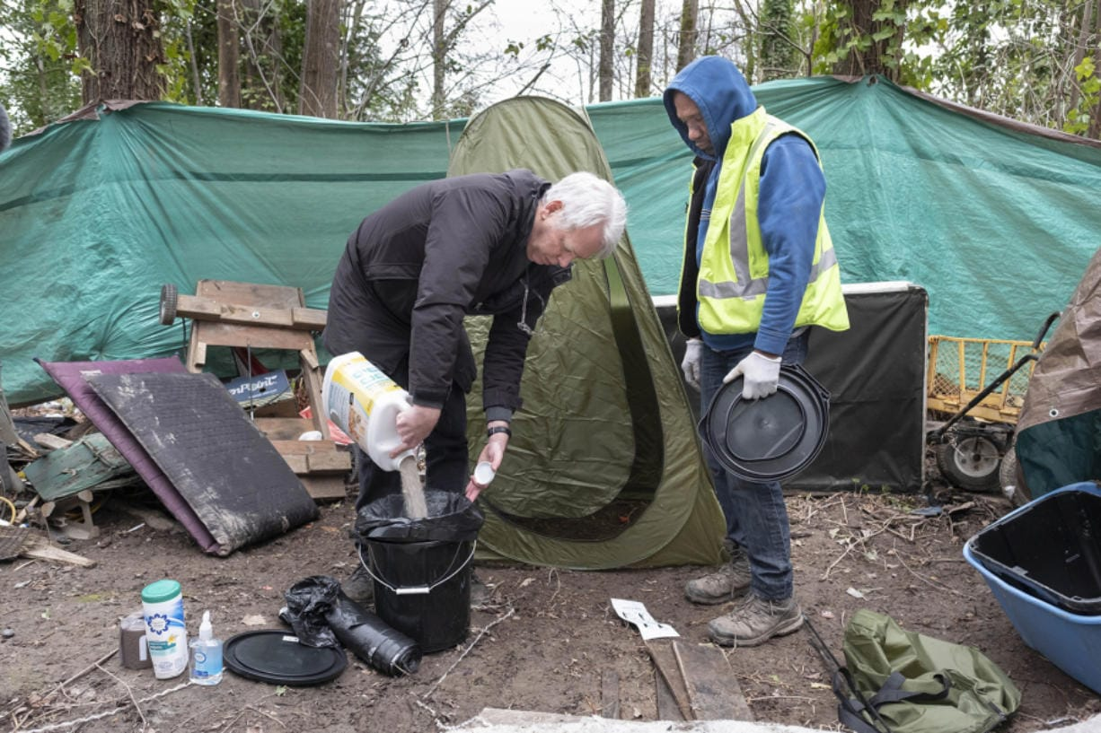 Mark Lloyd, left, shows Eric Smith how to hygenically manage a toilet he and others in his homeless camp can use on Tuesday. Smith is a homeless man who is doing what he can to keep his encampment clean. He's getting help from Lloyd who has provided some basic elements of sanitation few homeless sites have.