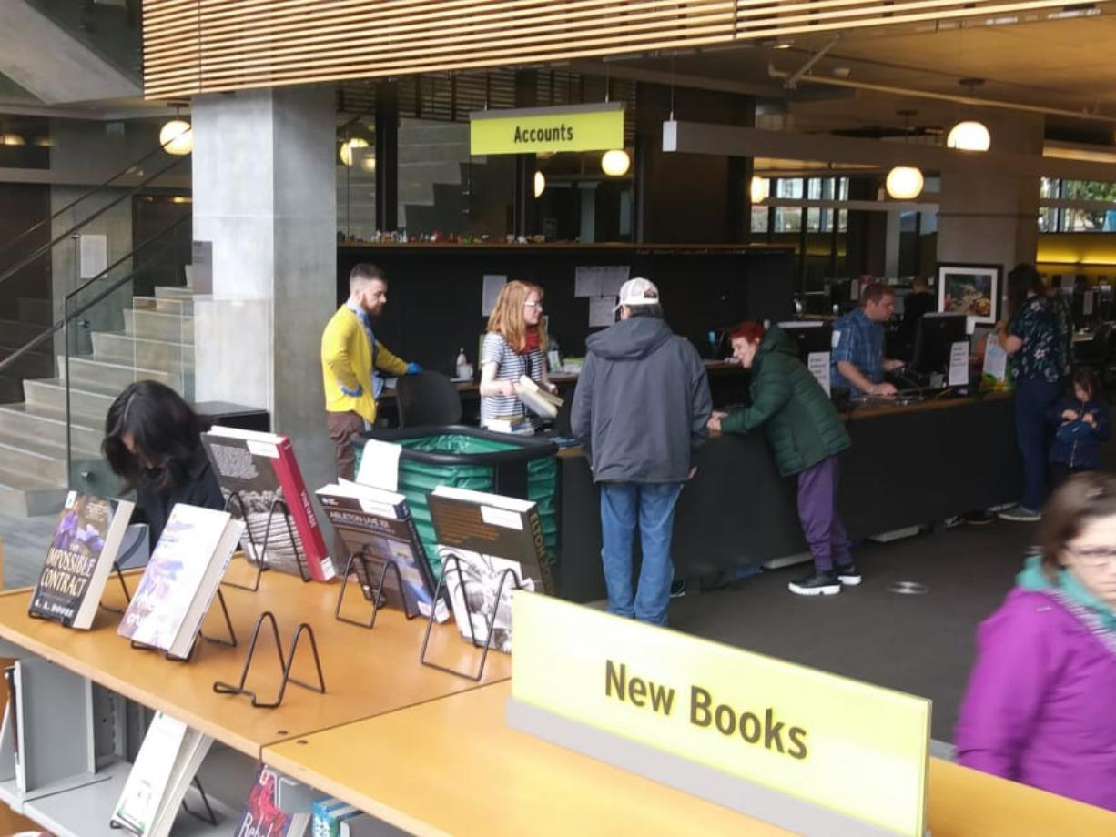 "Patrons scoured the Vancouver Community Library on Saturday for weeks' worth of materials to take home before the library closed for two weeks. ""It was crazy, crazy,"" said library access manager Brian Hulsey, in yellow. ""Every single thing was flying out the door."" (Scott Hewitt/The Columbian)"