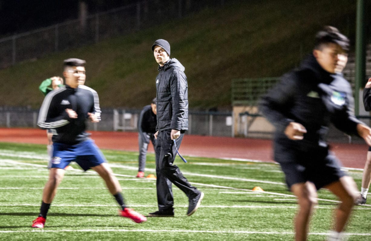 Mountain View coach Dustin Johnson walks through a conditioning drill during a late-night practice on March 11 at McKenzie Stadium. (Joshua Hart/The Columbian)