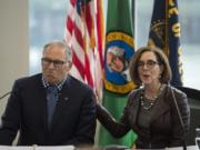 Washington Gov. Jay Inslee and Oregon Gov. Kate Brown talk to reporters before signing a memorandum of intent to replace the Interstate 5 Bridge during an event in November at the Murdock Charitable Trust in Vancouver. The governors have taken on bigger responsibilities during the coronavirus pandemic, which has lacked an efficient, uniform federal response.