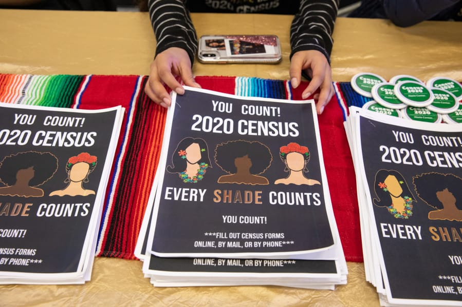 Alma Melchor, 17, a volunteer with the Southwest Washington Census Coalition, straightens a stack of information packets while working at a table at Expo Quinceanera NW on Feb. 29, 2020.