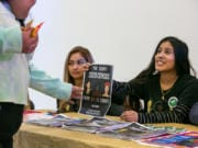 Alma Melchor, 17, right, and Carmen Huizar, center, both volunteers with the Southwest Washington Census Coalition, offer information about the importance of participating in the census to people arriving at Expo Quinceanera NW.