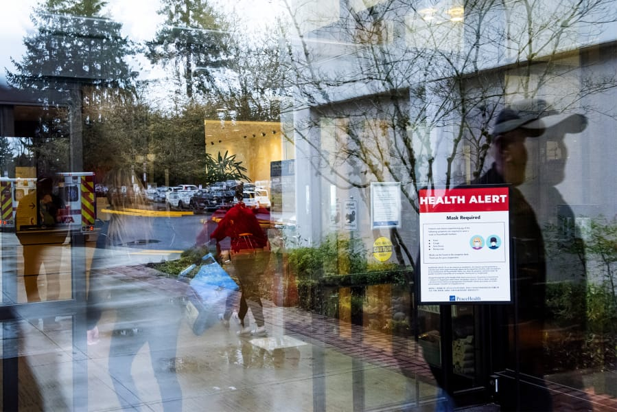 Visitors walk past a health alert sign with measures meant to prevent the spread of coronavirus at an entrance to PeaceHealth Southwest Medical Center in Vancouver. The hospital is implementing some protocols to help protect against the spread of COVID-19.