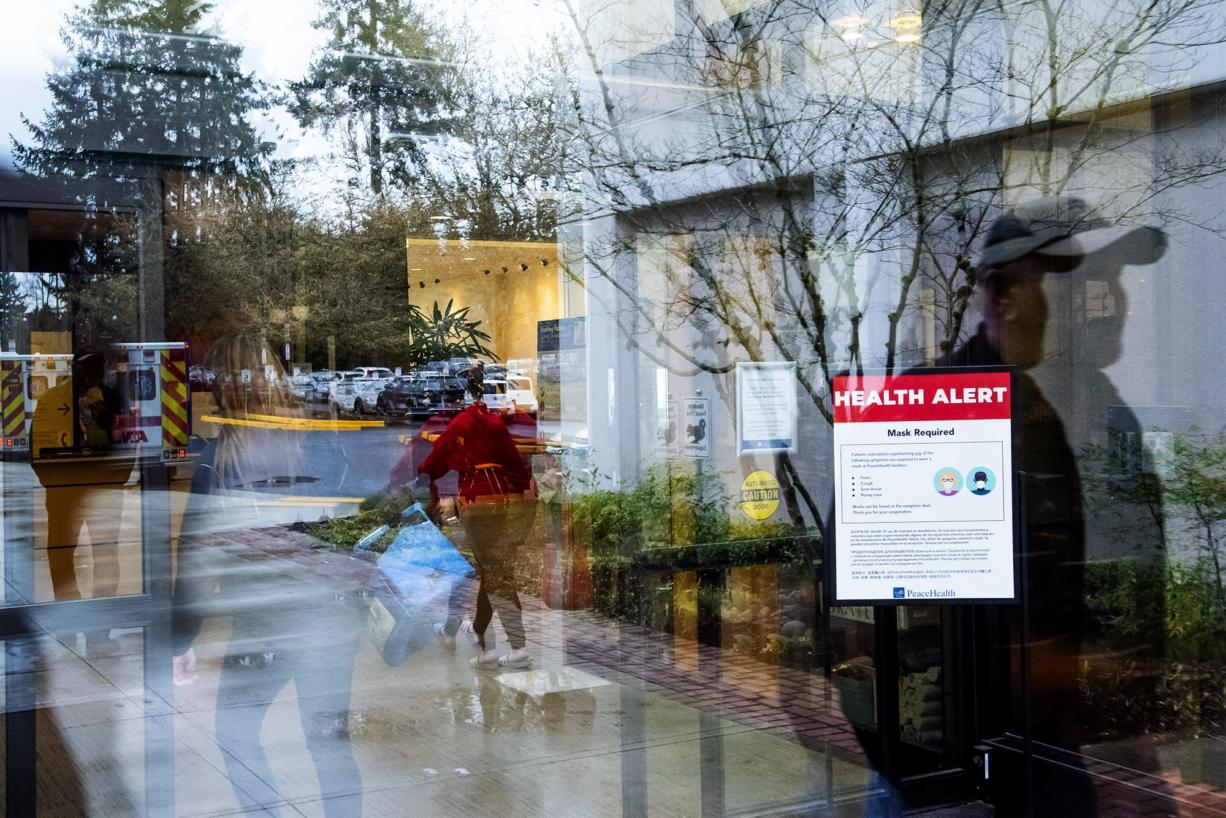 Visitors walk past a health alert sign with measures meant to prevent the spread of coronavirus at an entrance to PeaceHealth Southwest Medical on Monday afternoon, March, 2, 2020.