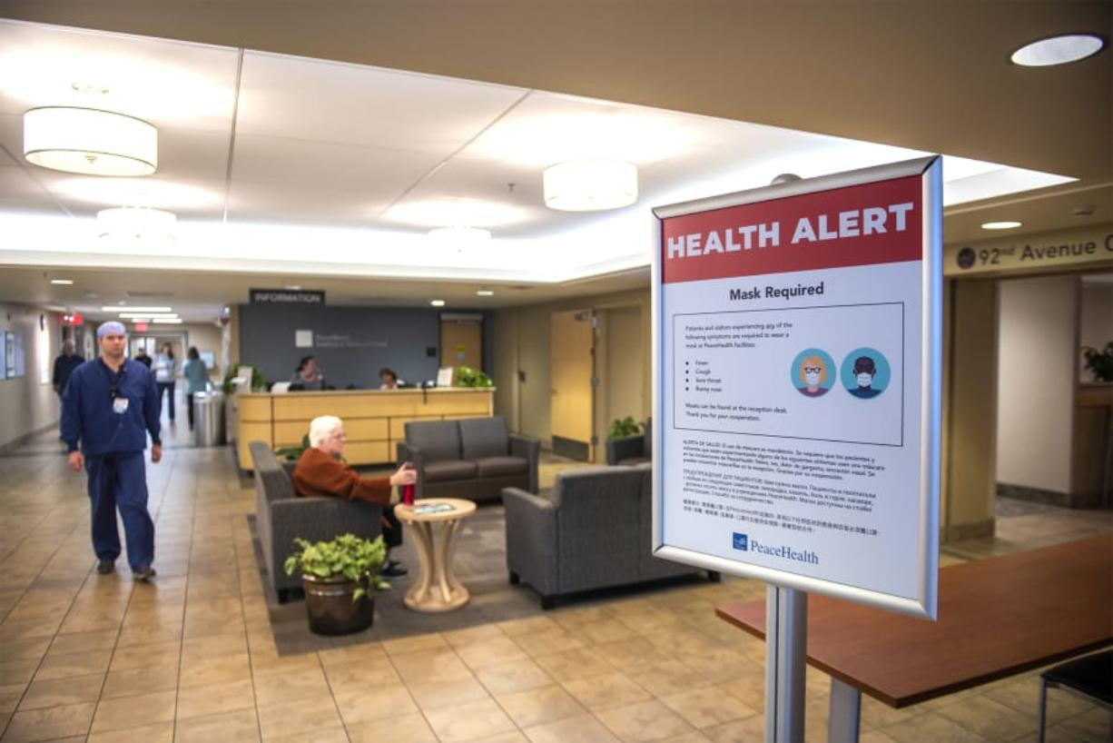 A medical worker walks past a sign informing visitors of health safety measures meant to prevent the spread of coronavirus at an entrance to PeaceHealth Southwest Medical on Monday afternoon.