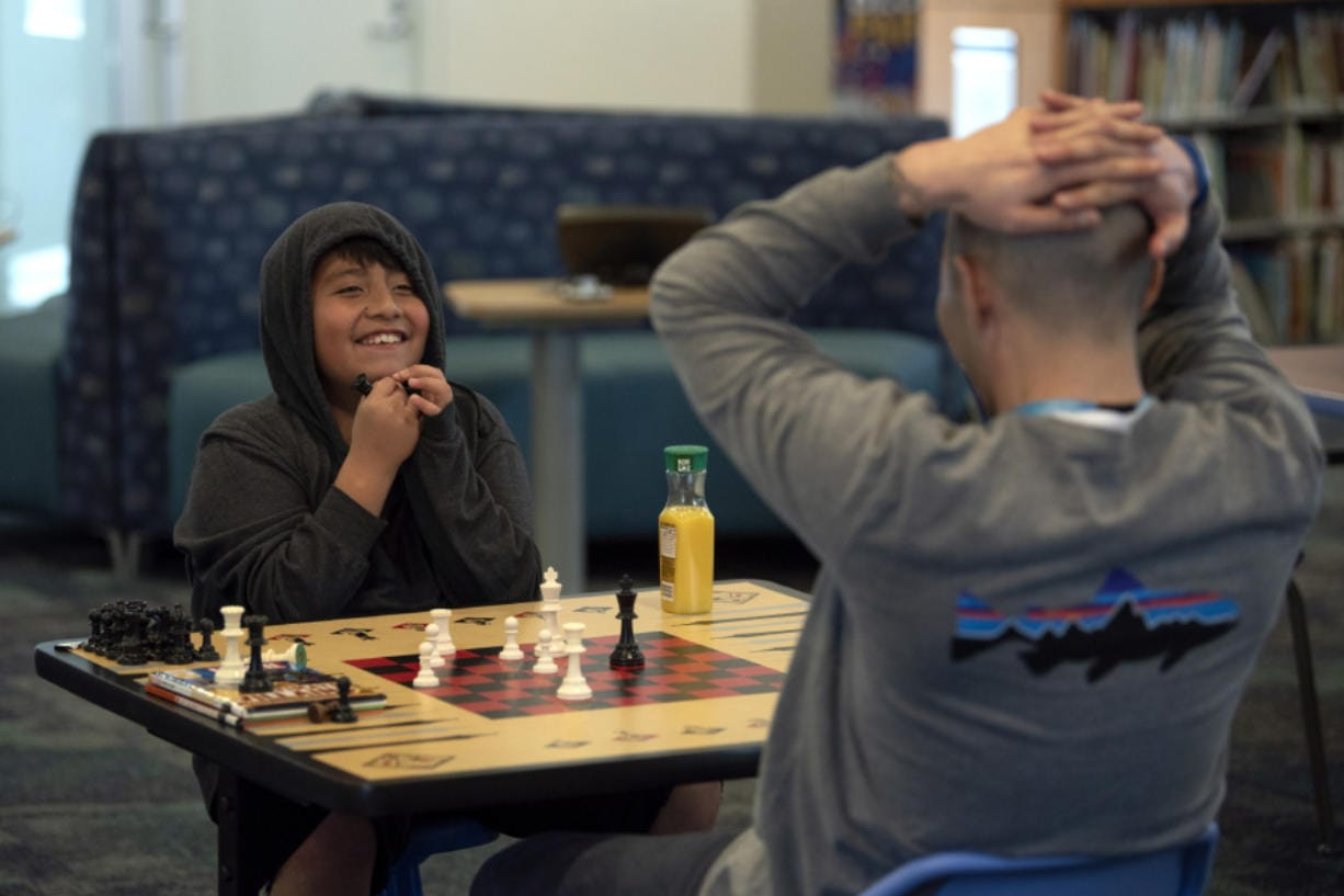 Luis, 10, reacts as he wins a game of chess against his mentor, Brian Kay, on Wednesday at Cascade Park Community Library in Vancouver. The duo were paired through Friends of the Children, a mentoring program that started in Portland in 1993.