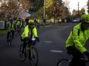 Cyclists practice riding single file and allowing sufficient space to avoid collisions while riding through Vancouver's Evergreen Highlands neighborhood on Monday night.