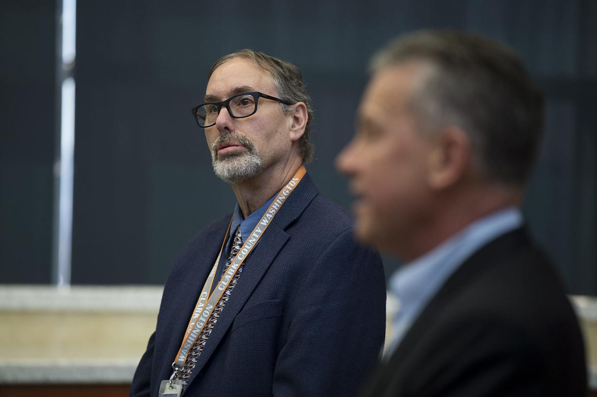 Dr. Alan Melnick, Clark County Health Officer and Public Health Director, left, listens as Clark County Councilor Gary Medvigy speaks to the media in March.