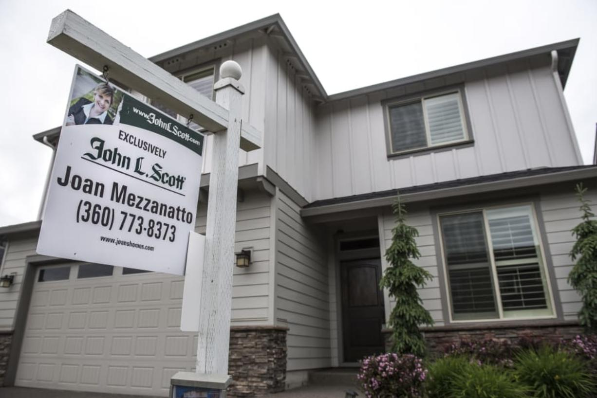 A for sale sign sits in front of a home in Felida in May. Clark County's housing market enjoyed a solid February. (Nathan Howard/The Columbian)