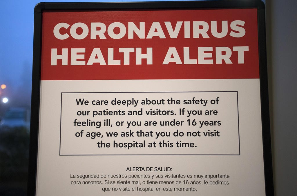 A coronavirus health alert sign is posted at one of the entrances to the Firstenburg Tower at PeaceHealth Southwest Medical Center on Monday morning, March 9, 2020. PeaceHealth has since gone to a no visitor policy. (Amanda Cowan/The Columbian)
