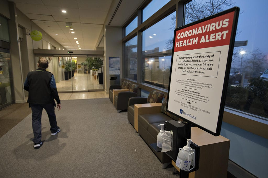 A man walks past a coronavirus health alert posted at one of the entrances to the Firstenburg Tower at PeaceHealth Southwest Medical Center on Monday morning.
