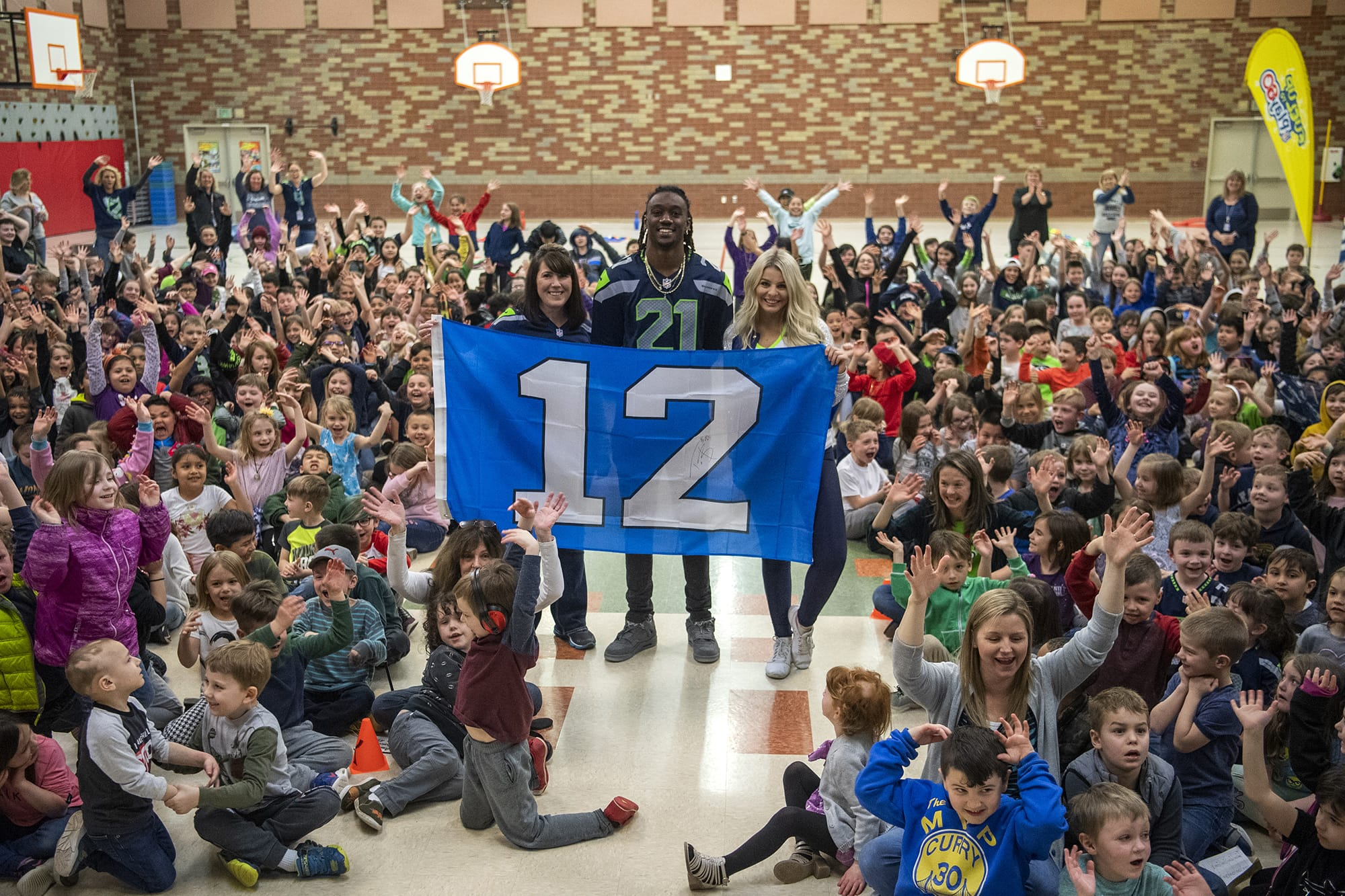 York Elementary School principle Dawn Harris, left, Seahawks cornerback Tre Flowers, center, and Seahawks dancer Kylie are pictured with the students at York Elementary School on Monday, March 9, 2020. The Dairy Farmers of Washington and the Seattle Seahawks visited the school on Monday to celebrate their new cafeteria milk dispensers. The self-serve milk dispensers use washable cups will help reduce the school's environmental impact.