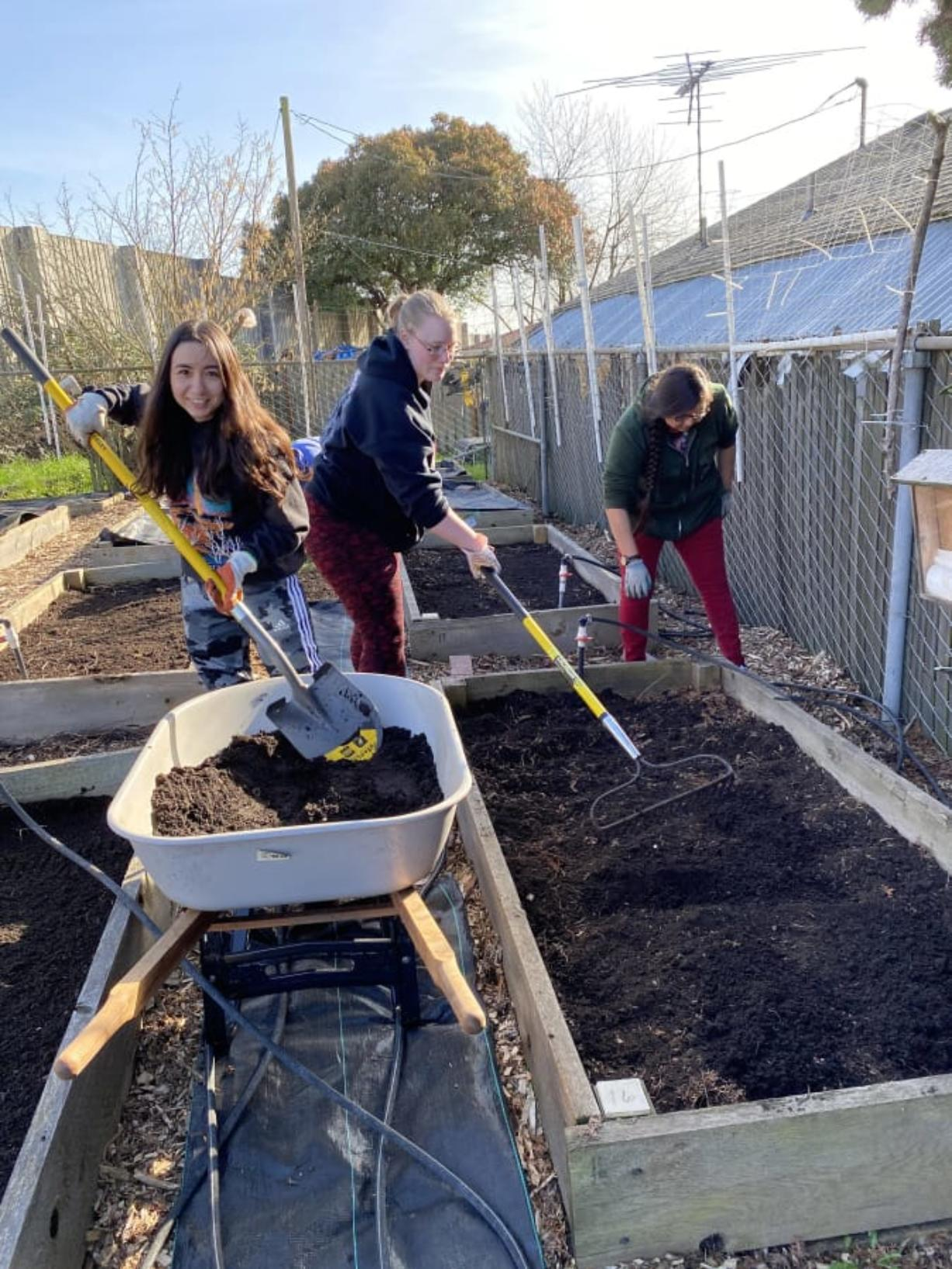 HAZEL DELL: From left, Karmia Keffer, Megan Ulrich, and Deborah Cronemeyer work at the Hazel Dell School and Community Garden. Thirty-seven Clark College student made a difference by helping prepare garden for spring.