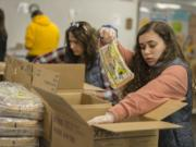 Volunteers Kirsten Humber, left, and her daughter, Delaney, 16, help put together emergency food boxes at the Clark County Food Bank on Wednesday afternoon.