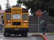 Owen Watt runs along side a school bus filled with fellow students as it pulls away from Covington Middle School on Friday afternoon, March 13, 2020.