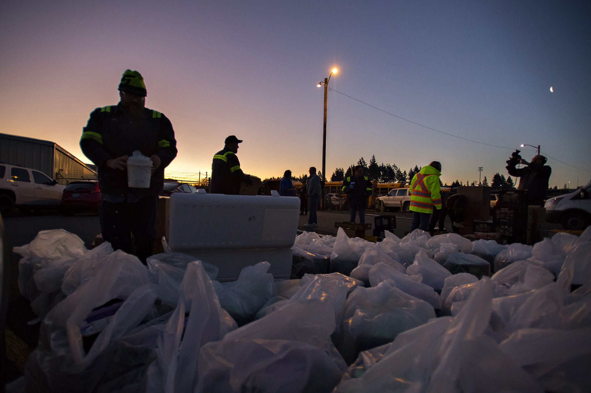 Michael Vestal, a mechanic with Evergreen School District, left, adds ice to boxes of milk near Burton Elementary School as the sun rises before drivers pick them up to be distributed to local students on Tuesday morning, March 17, 2020. (Amanda Cowan/The Columbian)