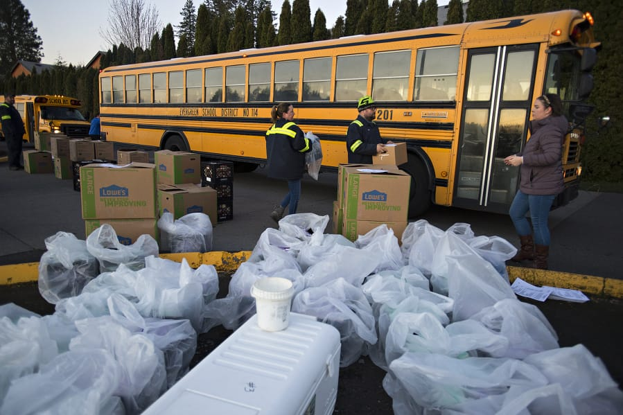Jenny Cook, from left, Michael Vestal and Simone Farabee of Evergreen Public Schools help load up milk and meals near Burton Elementary School to be delivered to local students on Tuesday morning.