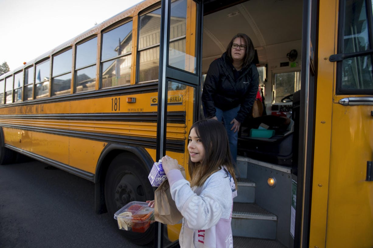 Kamryn Tanioka, 9, foreground, picks up her breakfast and lunch from school bus driver Tanisha Cardiel as she makes deliveries for students on her route in east Vancouver on Tuesday morning. Evergreen Public Schools is delivering meals to students by bus, and started the service on Tuesday.