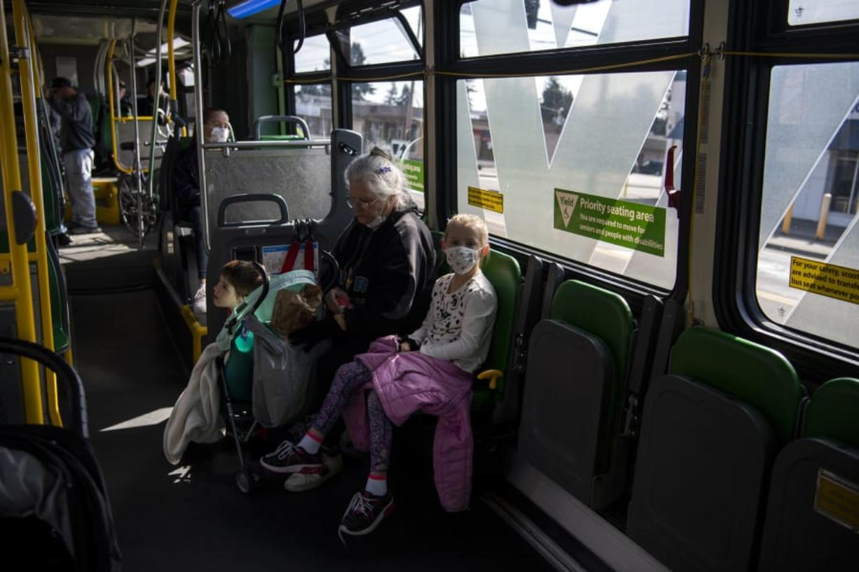 Linda Hilley of Vancouver rides The Vine on Wednesday with her grandchildren, Cali, 11, back left, Reno, 6, center, and Justice, 8, right. C-Tran reported a drop in ridership but has not reduced its routes. Hilley said she is watching her grandchildren because schools have been closed due to the novel coronavirus pandemic, and their parents are still working. (Photos by Alisha Jucevic/The Columbian)