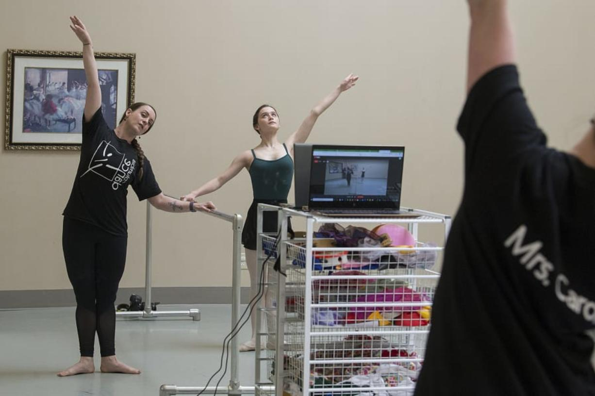Carol Arroyo, a ballet teacher at Columbia Dance Center, left, and her daughter, Ava, 13, livestream a ballet class in an empty studio for adults unable to attend due to the COVID-19 quarantine on Wednesday morning. The school is closed through April 24 due to the virus, which has closed schools across the state.