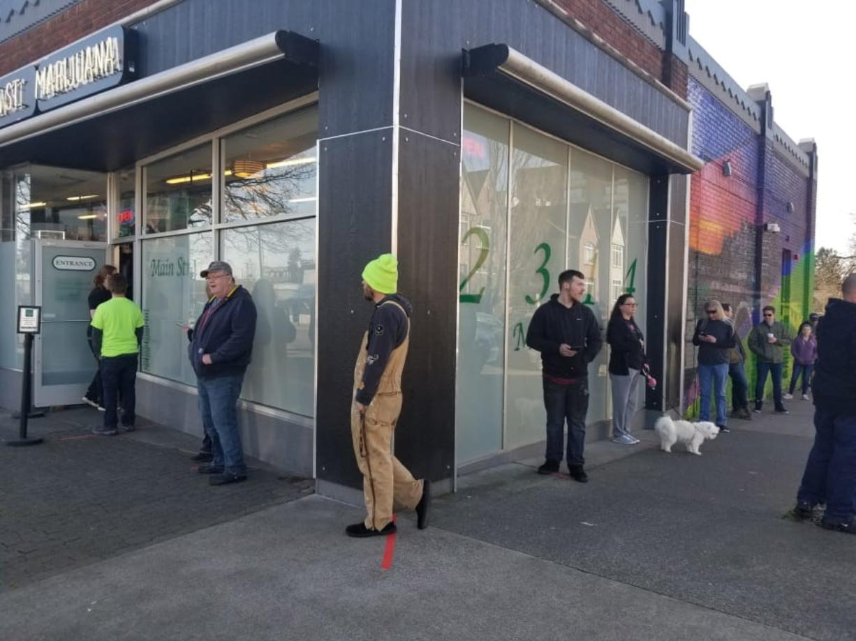 Customers stand in line outside Main Street Marijuana in downtown Vancouver on Monday afternoon. Employees placed strips of red duct tape on the ground inside and outside the store to help guide visitors to maintain the recommended 6-foot distances between them to reduce the risk of spreading COVID-19. (Anthony Macuk/The Columbian)