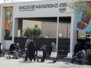 People form a line outside the Vancouver Navigation Center as they wait for their turn to come inside on Wednesday. Only 50 people at a time were allowed inside, an attempt to create more space between clients because of COVID-19 concerns.