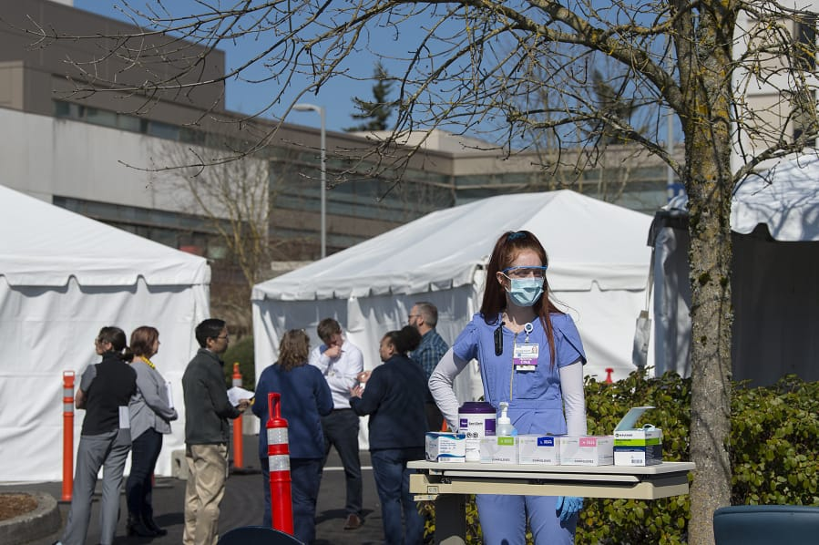 Certified nursing assistant Skye Jackson waits to greet incoming COVID-19 patients as staff in the emergency department meet to plan for a tent triage area at PeaceHealth Southwest Medical Center in Vancouver. The tents outside PeaceHealth are designed to separate possible COVID-19 cases from other emergency department patients. (Amanda Cowan/The Columbian)