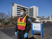 Frank Lopez, who works in security at PeaceHealth Southwest Medical Center in Vancouver, wears a mask and gloves as he waits to direct COVID-19 patients and other visitors Friday afternoon.