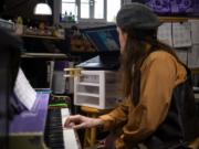 Jeffree White glances up at his laptop computer, where you can see piano student Daniel Martinez following the online lesson.