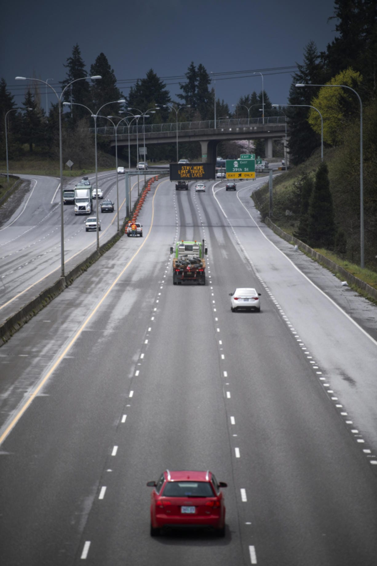 """A sparse but steady flow of vehicles moves under a sign on Interstate 5 reading """"STAY HOME, LIMIT TRAVEL, SAVE LIVES"""" in Vancouver on Tuesday. Gov. Jay Inslee issued a temporary stay-at-home order Monday evening to slow the spread of COVID-19."""